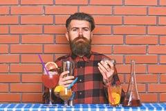 Alcoholisch drankenconcept De barman met lange baard en snor en het modieuze haar op de strikte schudbeker van de gezichtsholding stock afbeeldingen