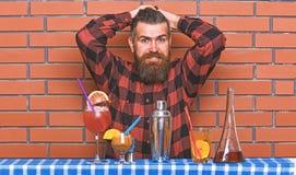 Alcoholisch drankenconcept De mens in geruit overhemd op bakstenen muurachtergrond bereidt dranken voor Barman met lange baard en stock foto's