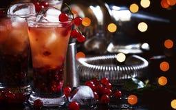 Alcoholische cocktail met likeur, jus d'orange en rode aalbes, zwarte lijst, selectieve nadruk stock foto