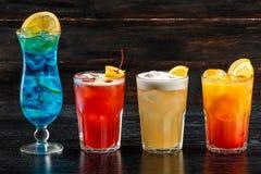 Alcoholische cocktailrij op hout backgroundks, kleurrijke partijdranken Reeks klassieke cocktails stock afbeeldingen