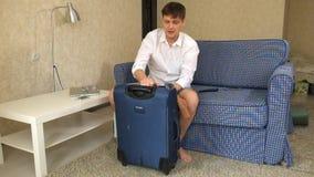 Alcoholische de echtgenoot verzamelt dingen in een koffer, vastmaakt het, zet zijn voeten op een koffer scheiding stock video