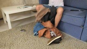 Alcoholische de echtgenoot werpt dingen uit een koffer, zoekend alcohol scheiding Close-up stock video