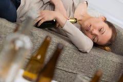 Alcoholische de holdingsflessen van de vrouwenslaap royalty-vrije stock fotografie