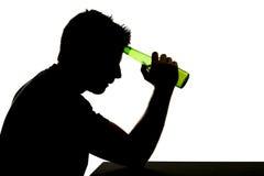 Alcoholische gedronken mens met bierfles in het silhouet van de alcoholverslaving stock foto's