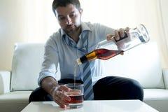 Alcoholische Zakenman die blauw gedronken overhemd dragen het opvullen van whiskyglas stock foto's