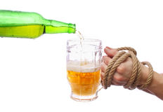 Alcoholism. Pouring beer into a mug, motion shot. Bound hands hold a glass Royalty Free Stock Image
