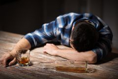 Drunk man with glass of alcohol on table at night. Alcoholism, alcohol addiction and people concept - male alcoholic with glass of whiskey and bottle lying or royalty free stock photos