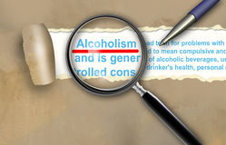 Alcoholism. Close-up of alcoholism with pen on it royalty free stock photography
