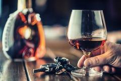 alcoholism Coloque o homem da mão do conhaque ou da aguardente as chaves ao carro fotografia de stock