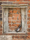 Alcoholism trouble. Alcoholism Concept. Empty beer bottle against old brick wall and window - dead end metaphor stock photo
