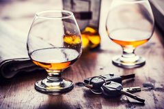 Alcoholism. Cup cognac or brandy hand man the keys to the car and irresponsible driver stock images