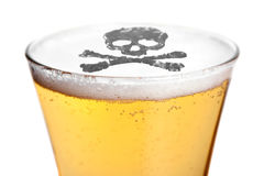 Alcoholism Is Deadly. The dangers of alcoholism concept with a skull and cross bones symbol floating on top of the beer stock image