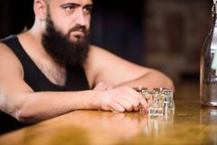 Alcoholism and depression. Guy spend leisure in bar with alcohol. Man drunk sit alone in pub. Alcohol addicted concept. Hipster brutal man drinking alcohol stock images