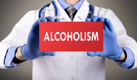 Alcoholism. Doctor`s hands in blue gloves shows the word alcoholism. Medical concept Royalty Free Stock Photography