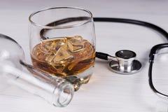 alcoholism Estetoscópio, vidro com conhaque uma garrafa vazia fotos de stock royalty free