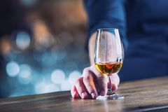Alcoholism. Hand alcoholic or barman and drink the distillate br. Andy or cognac royalty free stock photos