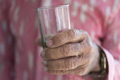 Alcoholism: Hand of Senior Holding a Glass of Rum Royalty Free Stock Photography