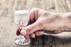 Alcoholism. Man hand alcoholic and drink the distillate Royalty Free Stock Photos