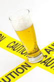 Alcoholism warning. Drinking addiction caution sign (Tall glass of cold beer on top of yellow caution tape Stock Images