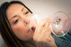 Alcoholism, woman drinking glass red wine. Party. Alcoholism, woman drinking glass red wine. A beautiful woman is in the home and is drinking a glass of red wine Stock Image