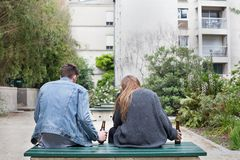 Alcoholism, young people drinking beer in park. Alcoholism, young people drinking beer on the bench Stock Image