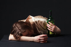 Alcoholism. Young woman is sleeping on the table. A bottle and a wineglass are in the hands stock photography