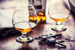 alcoholisme Kopcognac of de mens van de brandewijnhand de sleutels tot de auto en de onverantwoordelijke bestuurder stock afbeeldingen