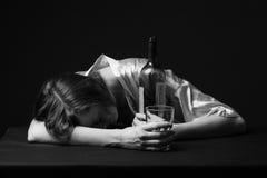 alcoholismo La mujer joven está durmiendo en la tabla Imagen de archivo libre de regalías