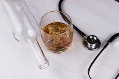 alcoholisms 听诊器,玻璃用科涅克白兰地一个空的瓶 库存图片