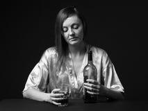 alcoholisms 少妇保留一个瓶和一个葡萄酒杯 免版税图库摄影
