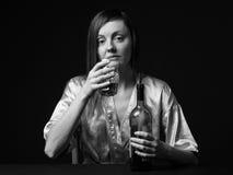 alcoholisms 少妇保留一个瓶和一个葡萄酒杯 库存图片