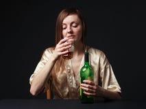 alcoholisms 少妇保留一个瓶和一个葡萄酒杯 免版税库存图片