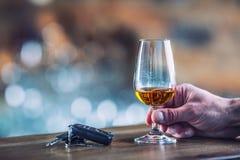 alcoholisms 杯科涅克白兰地或白兰地酒手人钥匙到的汽车 免版税库存照片