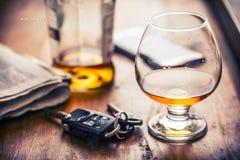 alcoholisms 杯科涅克白兰地或白兰地酒手人钥匙对汽车和不负责任的司机 免版税库存图片