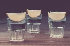 Alcoholschoten met een kalk op houten schoten als achtergrond/Alcohol met een kalk op houten achtergrond gestemd stock fotografie