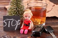 Alcool accanto alla bambola ed alle chiavi immagini stock