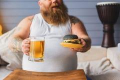 Alcool bevente del tipo spesso allegro con l'hamburger Immagini Stock Libere da Diritti