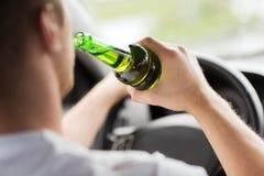 Alcool bevente dell'uomo mentre conducendo l'automobile Immagini Stock