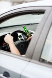 Alcool bevente dell'uomo mentre conducendo l'automobile Immagine Stock