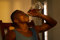 Alcool potable d'homme de couleur sans emploi désespéré à la maison seulement Image libre de droits