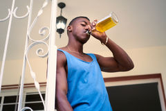 Alcool potable d'homme de couleur sans emploi seul à la maison Photos stock