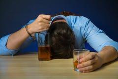 Alcool potable d'homme ivre à la table photos stock
