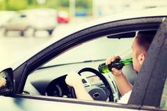 Alcool potable d'homme tout en conduisant la voiture Photographie stock libre de droits