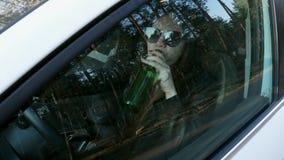 Alcool potable de femme se reposant derri?re la roue d'une voiture, offense du trafic banque de vidéos