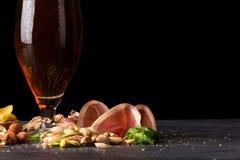 Alcool, prosciutto di Parma e dadi su un fondo nero della tavola Un vetro di birra scura, fredda, fresca e di carne tagliata Copi Immagini Stock