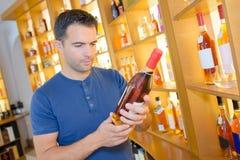 Alcoolici della bottiglia della tenuta dell'uomo in distilleria fotografia stock