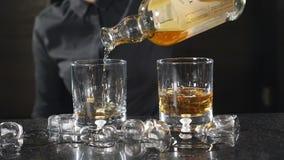 Alcoolici di versamento del barista femminile dalla bottiglia in vetro al rallentatore Una barra in night-club Un barista in unif video d archivio