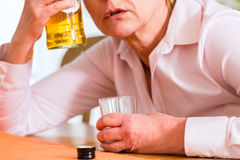 Alcoolique féminin buvant la boisson alcoolisée dure Photographie stock libre de droits