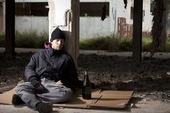 Alcoolique s'asseyant sur l'étage Images stock