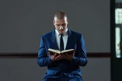 Alcorão muçulmano do livro de Reading Holy Islamic do homem de negócios fotografia de stock